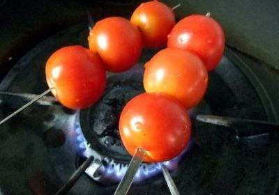 直火にかざしてトマトの皮をむく